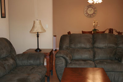 The living room seats several people comfortably with plush new couches and chairs. Each home includes a flat screen TV with DVD player for relaxing during downtime.